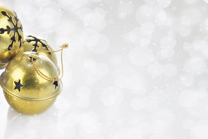 Gold Jingle bells on a snowy bokeh s