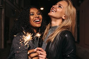 Two happy girlfriends with sparklers
