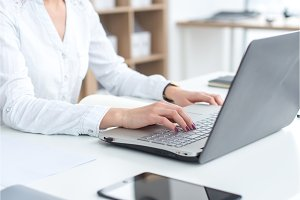 Businesswoman typing on laptop at