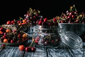 ripe sweet cherries in glass jar and