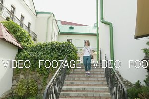 Young woman walk down on stairs.