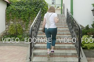 Young woman running on stairs.