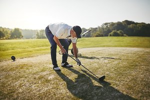 Senior golfer placing his ball on a