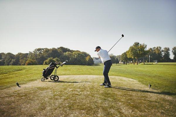 Senior man hitting his golf ball wi…