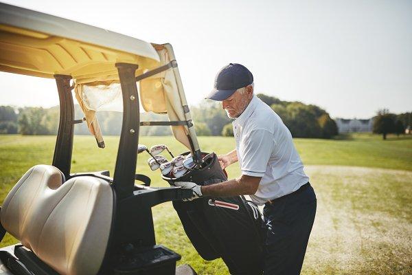 Senior golfer placing his golf club…