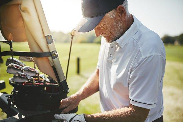 Senior man looking through his golf…