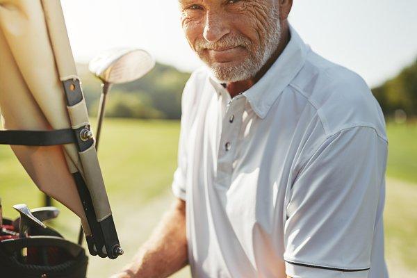 Smiling senior man looking through…
