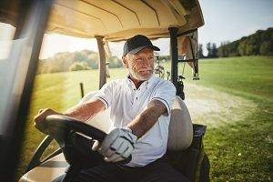 Senior man driving his golf cart on