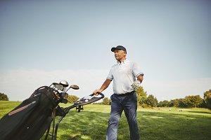 Senior man pushing his golf clubs on