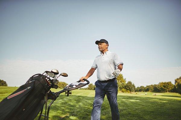Senior man pushing his golf clubs o…
