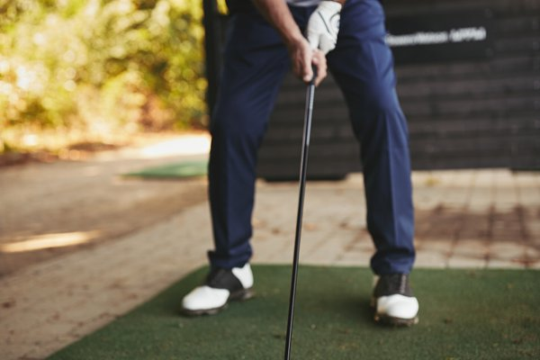 Senior man practicing golf at a dri…