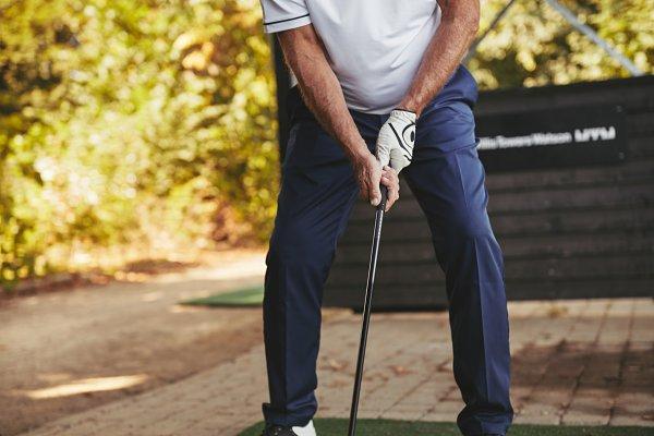 Senior man practicing his swing at…