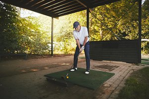 Sporty senior man practicing golf at