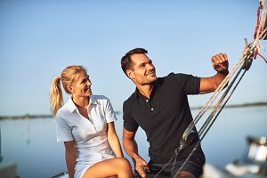 Smiling young couple sailing their y