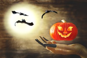 Witch's hand with a flying pumpkin