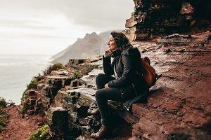 Female traveler relaxing on rocky