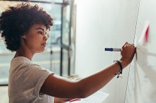 Woman writing on white board by  in Business
