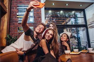 Excited friends taking selfie with