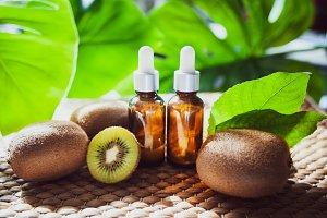 Bottles with  kiwi oil, fresh  fruit