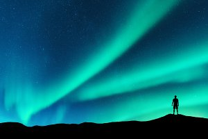 Aurora and silhouette of alone man