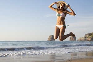 Happy woman jump at beach