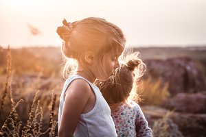 two little girls in a field at sunse