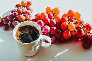 Coffee and grapes on white table