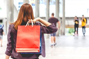 Woman holding shopping bag walking