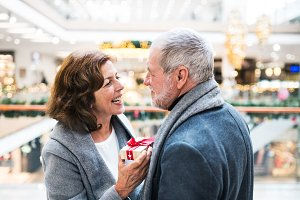 A senior man giving a present to a