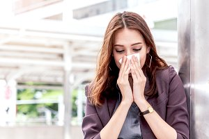Sick business woman with sneezing