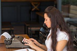 Female using vintage typewriter.