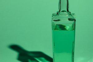 glass bottle of absinthe on green su