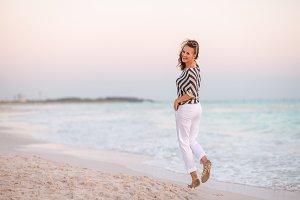 modern woman on seashore at sunset w