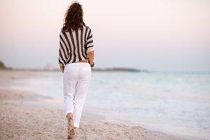modern woman on seacoast at sunset w