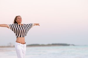 trendy woman on seacoast in evening