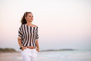 modern woman on seacoast at sunset l