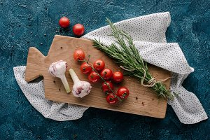 Wooden board with tomatoes and garli