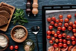 Pan with cherry tomatoes on dark woo
