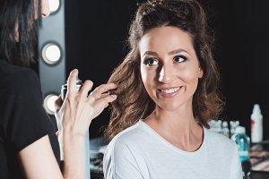 hair dresser using hair spray to fin