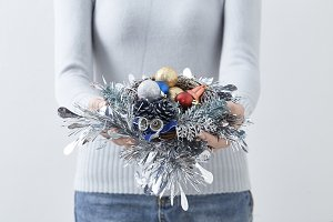 Female hand holding Christmas wreath