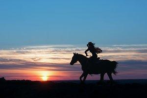 Mounted postman running on sunset
