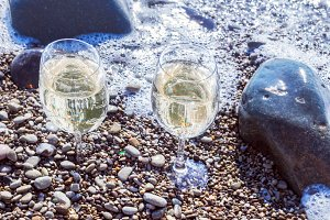 Glasses of white wine by sea