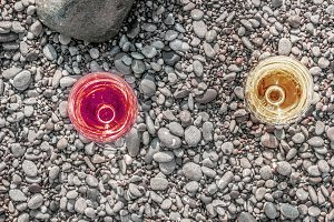 Two glasses of wine on sea pebbles