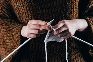 cropped view of woman knitting white