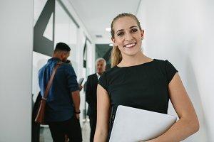 Happy woman in office corridor