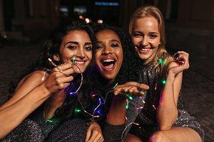 Happy women holding christmas lights