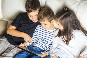 Three kids using a tablet at home