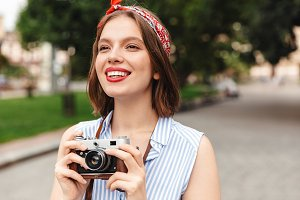 Smiling hipster woman holding retro