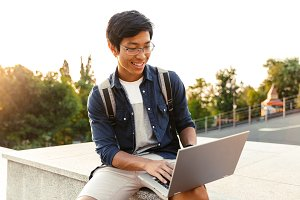 Smiling asian man student with backp