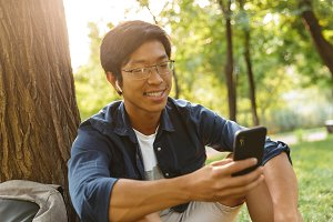 Happy asian male student in eyeglass